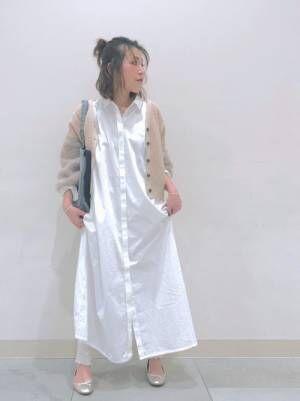 白のシャツワンピ、白のリブレギンスにベージュのカーディガンを着た女性