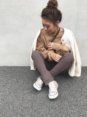 ベージュのスウェット、ブラウンのリブレギンスに白のキルティングジャケットを羽織った女性