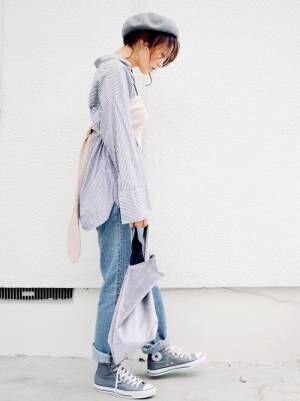 ブルーのストライプシャツにビスチェを合わせて、淡色デニムを合わせた女性