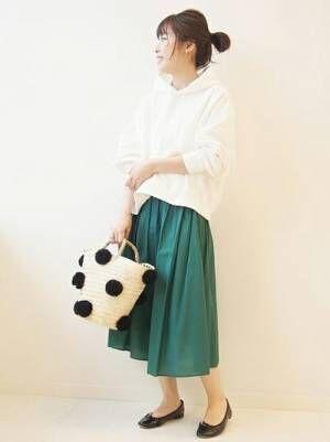 白のパーカーにグリーンのフレアスカートを合わせた女性