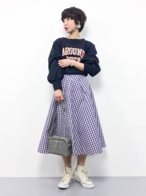 ネイビーのスウェットにパープルのギンガムチェックのフレアスカートを合わせた女性