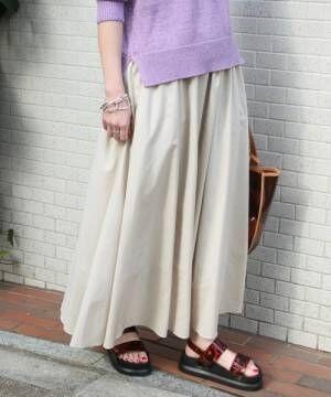パープルニットに生成色のフレアスカートを履いた女性