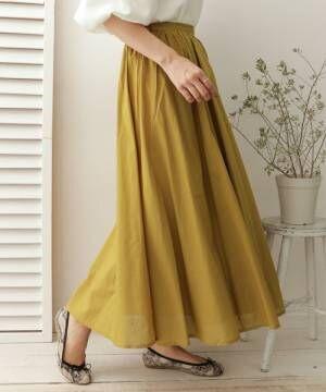 くすみイエローのフレアスカートを履いた女性