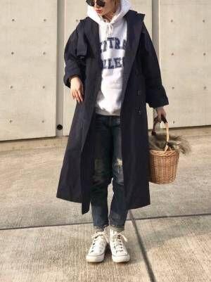 グレーのロゴパーカー、デニムパンツにネイビーのトレンチコートを着た女性
