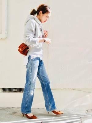 グレーのロゴパーカーにデニムパンツを履いた女性
