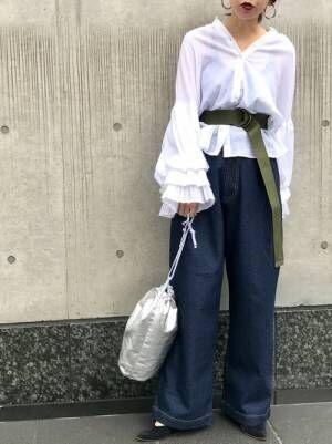 白のシャツにデニムワイドパンツを履いた女性