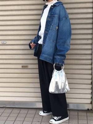 白のブラウス、黒のワイドパンツにGジャンを着た女性