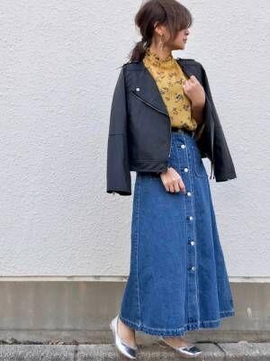 黄色の花柄ブラウス、デニムスカートにライダースジャケットを羽織った女性