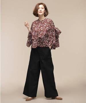 ボルドーの花柄ブラウスに黒のワイドパンツを履いた女性