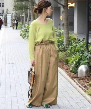 ライムグリーンのニットにベージュパンツを履いた女性
