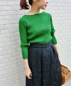 グリーンのリブニットにネイビーレーススカートを履いた女性