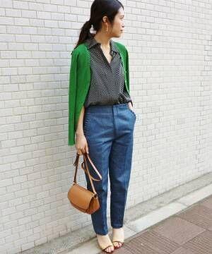 ドットシャツにグリーンカーデとデニムパンツを着た女性
