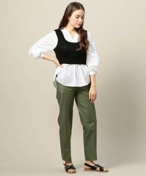 白いシャツにグリーンのパンツを合わせてニットビスチェを着た女性