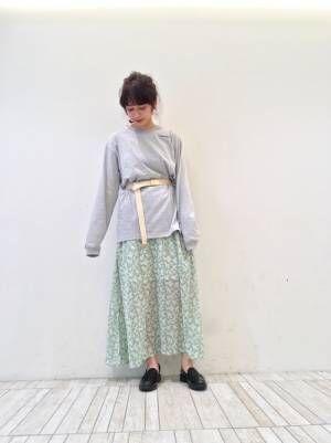 グレーのスウェットにグリーンのスカートを合わせて黒いローファーを履いた女性