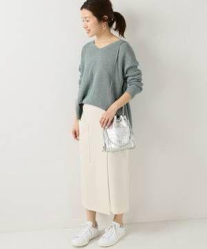 ミントグリーンのニットに白いスカートを合わせて白いスニーカーを履いた女性