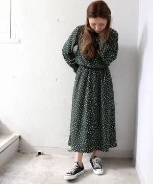 グリーンのドットワンピースを着て黒いスニーカーを履いた女性
