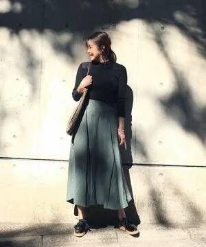 黒いトップスにオリーブのスカートを合わせて黒いフラットシューズを履いた女性