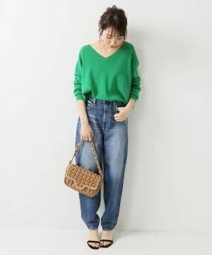 グリーンのニットにデニムを合わせてかごバッグを持った女性