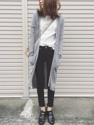 白のトップス、黒のスキニーパンツにグレーのロングカーディガンを着た女性