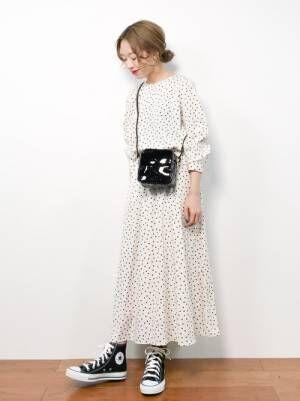 白のドット柄ワンピースを着た女性