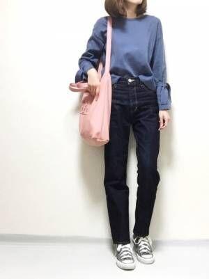 ブルーのトップスにデニムを合わせてピンクのトートバッグを持った女性