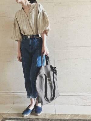 ストライプのブラウスにデニムを合わせてグレーのトートバッグを持った女性