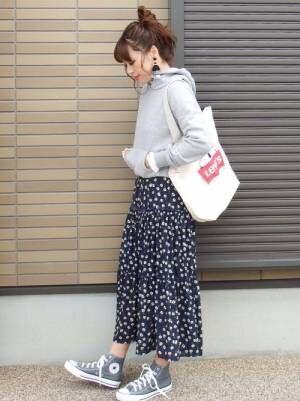グレーのスウェットに花柄スカートを合わせてトートバッグを持った女性