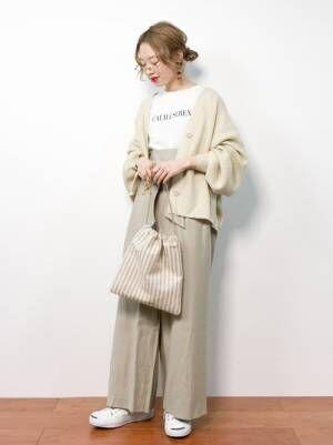 白のトップス、ベージュのワイドパンツにベージュのカーディガンを着た女性
