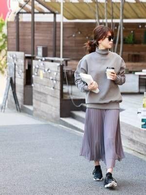 グレーのスウェットにグレーのプリーツスカートを履いた女性