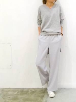 グレーのニットにグレーのパンツを履いた女性