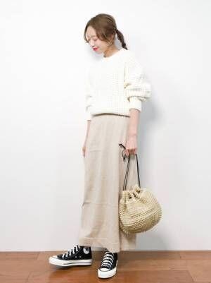白ニットにベージュのロングスカートを履いた女性