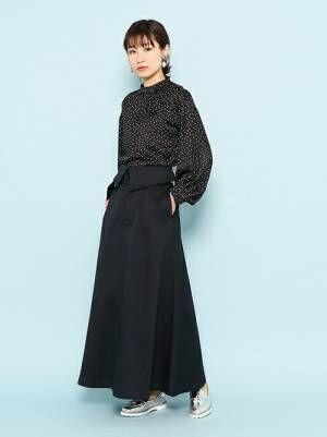 黒のドット柄ブラウスにネイビーのフレアスカートを履いた女性