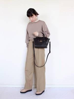 ベージュのスウェットにベージュのワイドパンツを履いた女性
