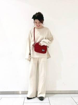 白のスウェットに白のスリットパンツを履いた女性