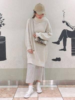 ベージュのチュニックに白のドット柄スカートを履いた女性