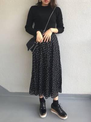 黒のトップスに黒のドット柄スカートを履いた女性