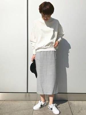 NIKEスニーカーとグレータイトスカートを着た女性