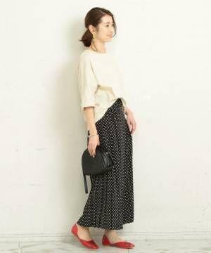 白のトップスに黒のドット柄プリーツスカートを履いた女性
