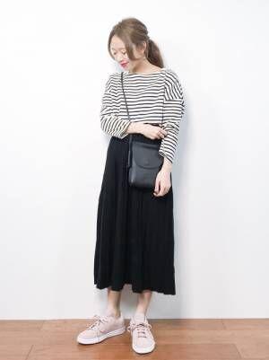 ボーダートップスに黒のプリーツスカートを履いた女性