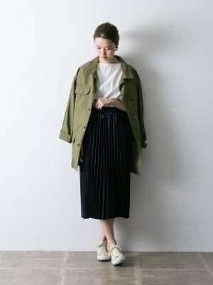 白のトップス、黒のプリーツスカートにカーキのコートを羽織った女性