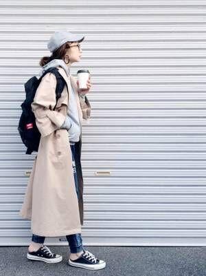 グレートップスにデニムを合わせてトレンチコートを着た女性