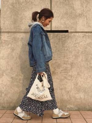 パーカーにデニムジャケットを合わせて花柄スカートを履いた女性