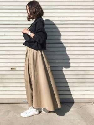 黒トップスにベージュのスカートを合わせて白いスニーカーを履いた女性