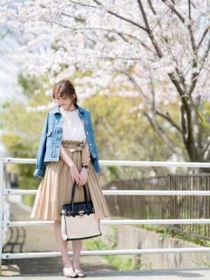 白ブラウスにデニムジャケットを羽織ったお花見女子