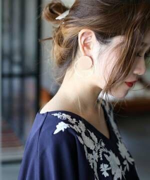 サークルタイプのウッドモチーフのイヤリングをした女性