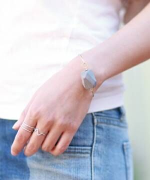 指輪とウッドパーツのバングルをつけた女性の手