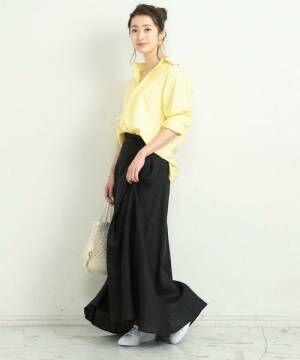 黄色いシャツに黒いスカートを合わせて白いスニーカーを履いた女性