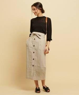 黒いブラウスにベージュのスカートを合わせて黒いサンダルを履いた女性