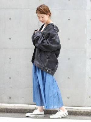 黒いデニムジャケットにブルーのスカートを合わせた女性