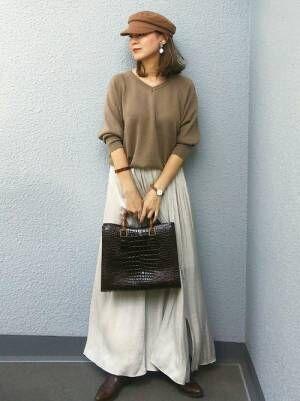 ブラウンのニットに白いスカートを合わせてブラウンのバッグを持った女性